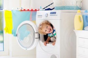 kid playing with clothes dryer